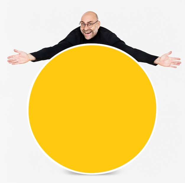 Hombre feliz mostrando un tablero amarillo redondo