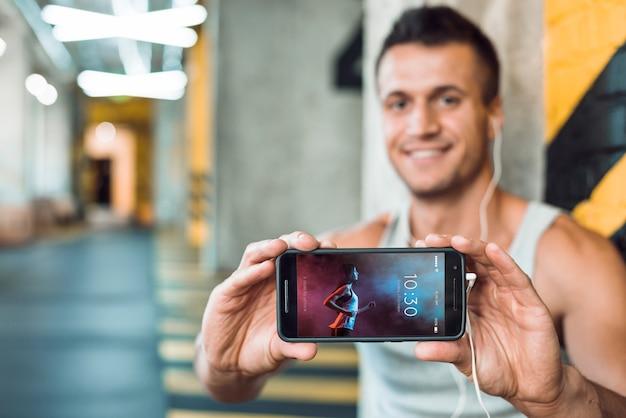 Hombre en gimnasio sujetando mockup de smartphone