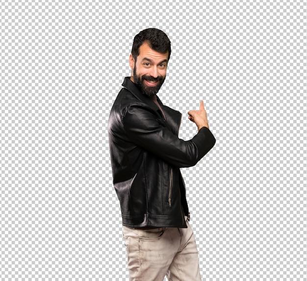 Hombre guapo con barba apuntando hacia atrás