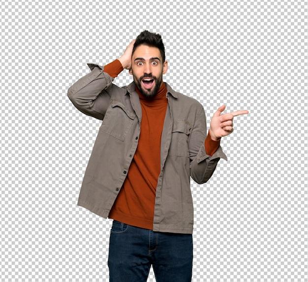 Hombre guapo con barba apuntando con el dedo hacia un lado y presentando un producto