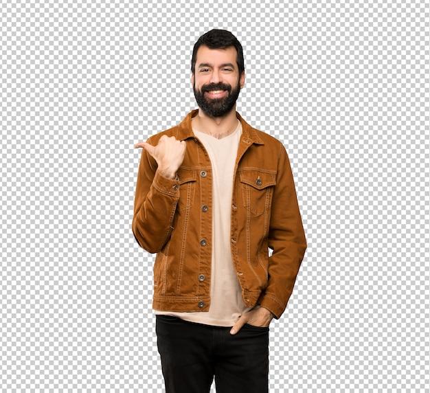 Hombre guapo con barba apuntando hacia un lado para presentar un producto.