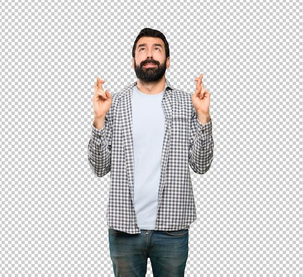 Hombre guapo con barba con los dedos cruzados y deseando lo mejor
