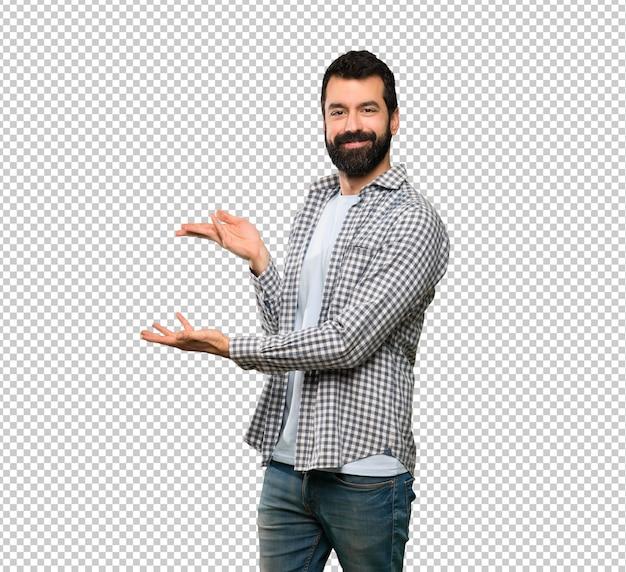 Hombre guapo con barba extendiendo las manos hacia un lado para invitar a venir