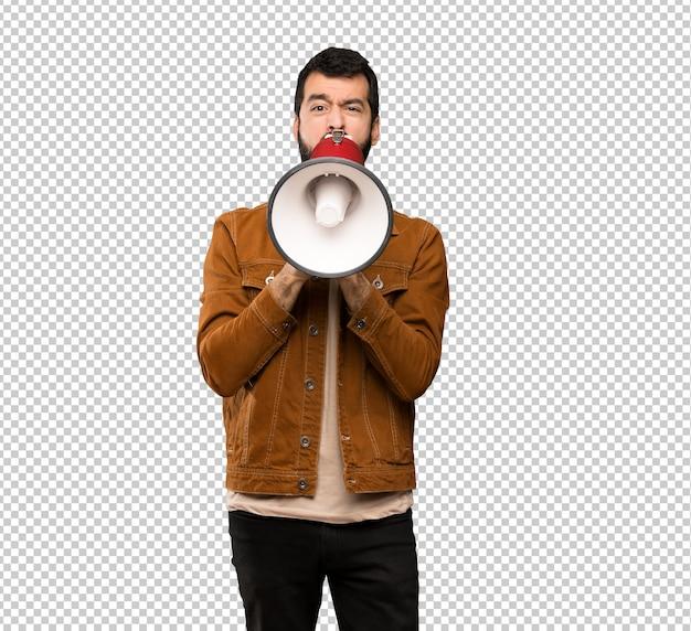Hombre guapo con barba gritando a través de un megáfono