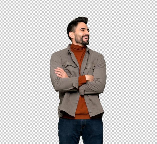 Hombre guapo con barba manteniendo los brazos cruzados mientras sonríe
