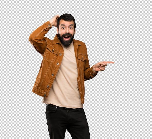 Hombre guapo con barba sorprendido y apuntando el dedo hacia un lado.