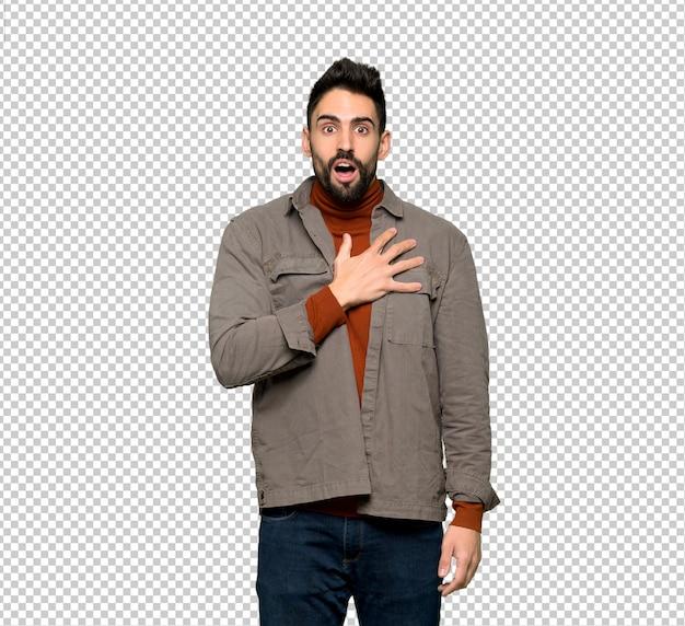 Hombre guapo con barba sorprendido y sorprendido mientras mira a la derecha