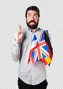 Hombre guapo con barba sosteniendo muchas banderas y con sus dedos cruzando