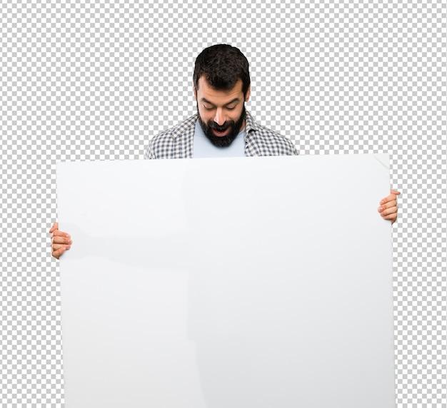 Hombre guapo con barba sosteniendo una pancarta vacía