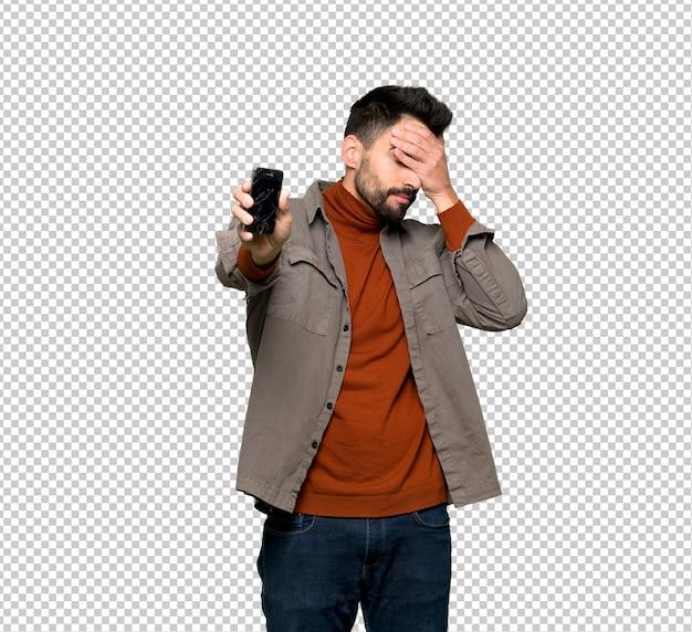 Hombre guapo con barba con teléfono inteligente roto con problemas