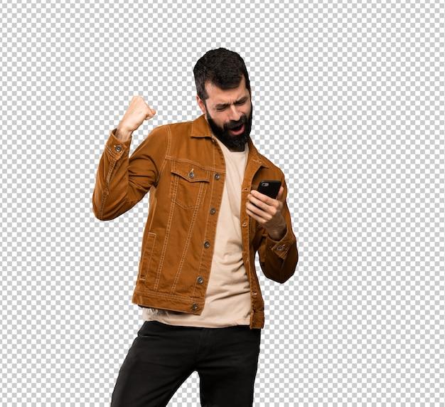 Hombre guapo con barba con teléfono en posición de victoria