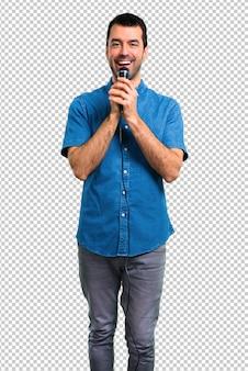 Hombre guapo con camisa azul cantando con micrófono