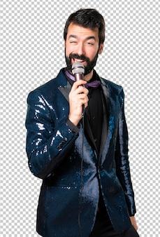 Hombre guapo con chaqueta de lentejuelas cantando con micrófono
