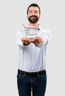 Hombre guapo feliz con barba sosteniendo un juguete de carrito de supermercado