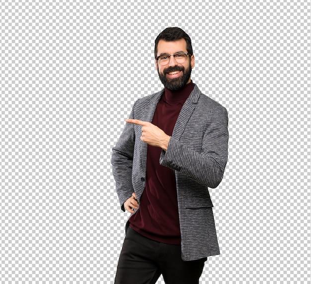Hombre guapo con gafas apuntando al costado para presentar un producto.