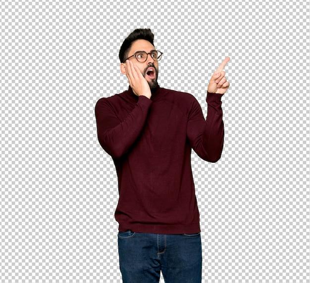 Hombre guapo con gafas apuntando hacia arriba y sorprendido