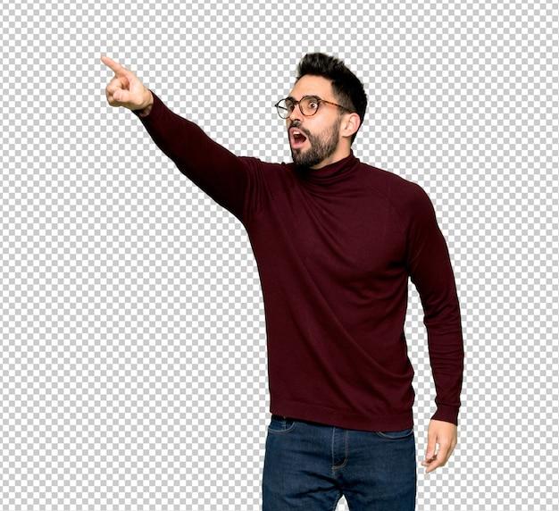 Hombre guapo con gafas apuntando lejos
