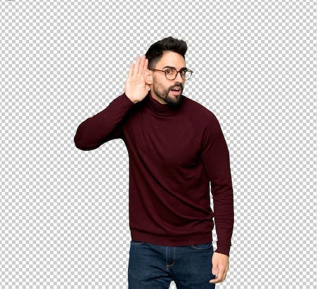 Hombre guapo con gafas escuchando algo poniendo la mano en la oreja