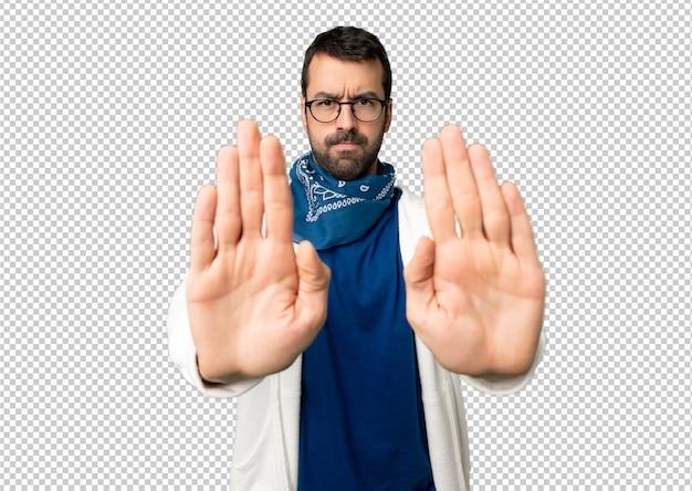 Hombre guapo con gafas haciendo gesto de parada para decepcionado con una opinión