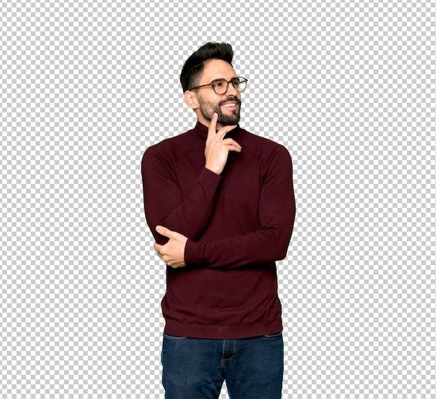 Hombre guapo con gafas pensando en una idea mientras mira hacia arriba