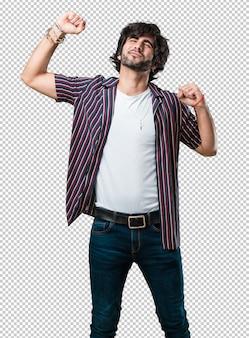 Hombre guapo joven escuchando música, bailando y divirtiéndose, moviéndose, gritando y expresando felicidad, concepto de libertad