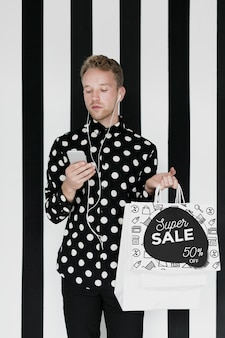 Hombre guapo maqueta sosteniendo bolsas de compras