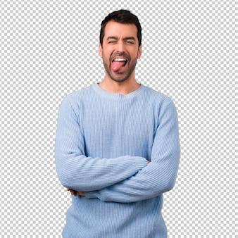 Hombre guapo mostrando la lengua en la cámara con mirada divertida