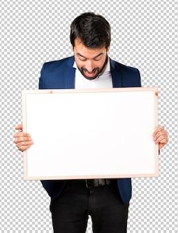 Hombre guapo sosteniendo un cartel vacío