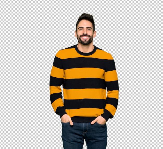 Hombre guapo con suéter a rayas posando y riendo mirando al frente
