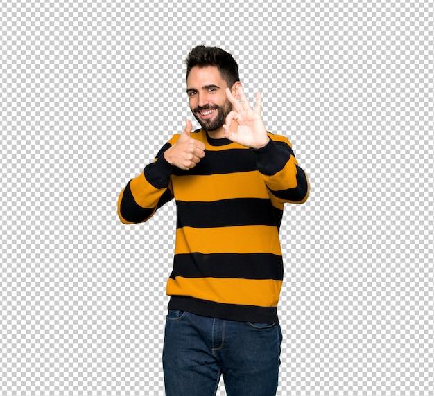 Hombre guapo con suéter a rayas que muestra el signo correcto con y dando un pulgar hacia arriba gesto