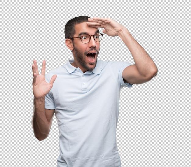 Hombre joven asombrado con un gesto de mirar lejos con su mano