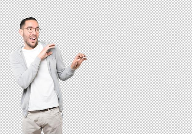 Hombre joven asustado que grita contra superficie transparente