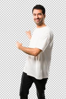Hombre joven con camisa blanca apuntando hacia atrás con el dedo índice presentando un producto desde atrás