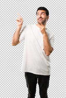 Hombre joven con camisa blanca apuntando con el dedo índice una gran idea y mirando hacia arriba