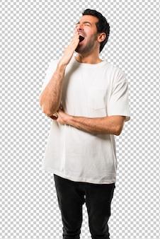 Hombre joven con la camisa blanca que bosteza y que cubre boca abierta con la mano. expresión somnolienta