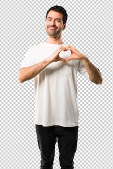 Hombre joven con la camisa blanca que hace símbolo del corazón por las manos. estar enamorado