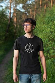 Hombre joven con una camiseta de maqueta en la naturaleza