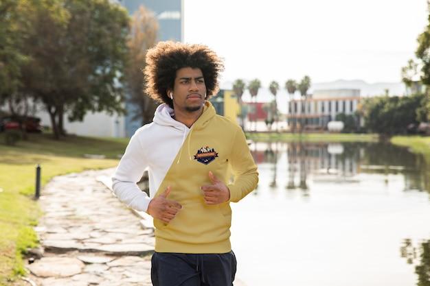 Hombre joven con capucha corriendo al aire libre