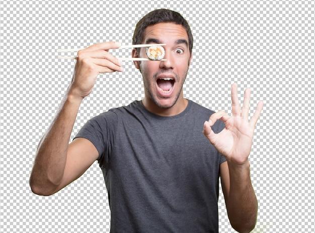 Hombre joven comiendo sushi