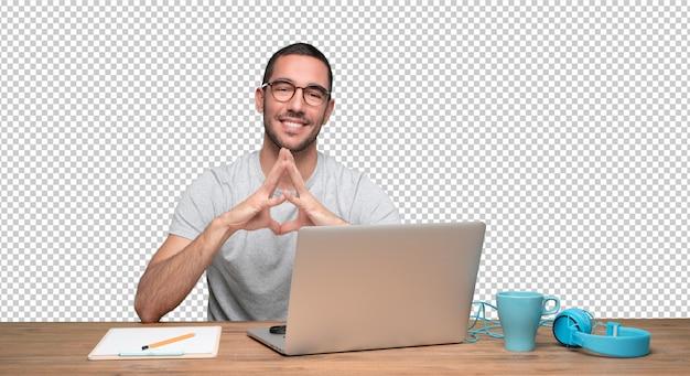 Hombre joven confidente que se sienta en su escritorio