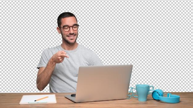 Hombre joven confidente que se sienta en su escritorio y que señala con su mano