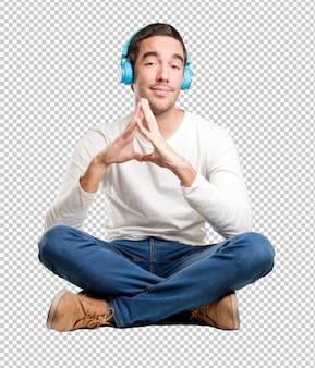 Hombre joven dudoso sentado usando auriculares