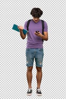 Hombre joven estudiante sorprendido y enviando un mensaje