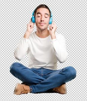 Hombre joven feliz asentado que usa auriculares