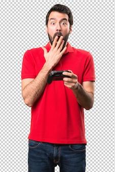Hombre joven hermoso que juega videojuegos y que hace gesto de la sorpresa
