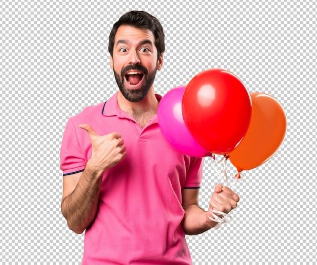 Hombre joven hermoso que sostiene los globos y con el pulgar para arriba