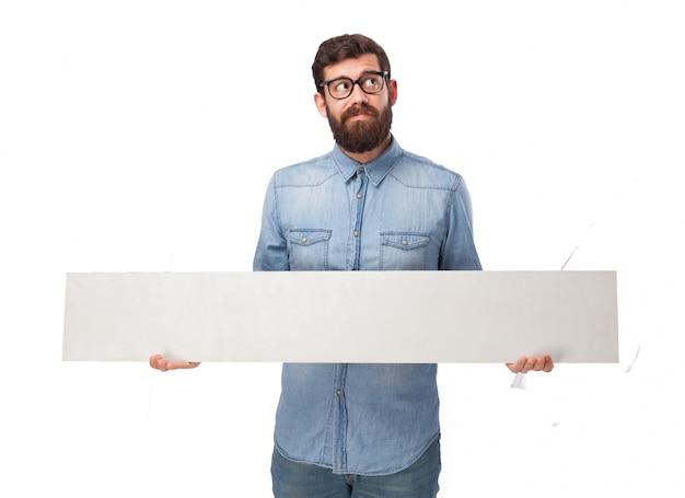 Hombre joven pensativo con un panel en blanco