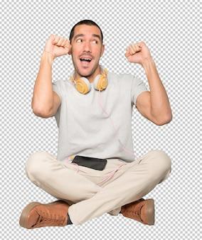Hombre joven en posición sentada con un gesto de celebración
