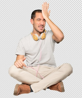 Hombre joven en posición sentada con un gesto de preocupación