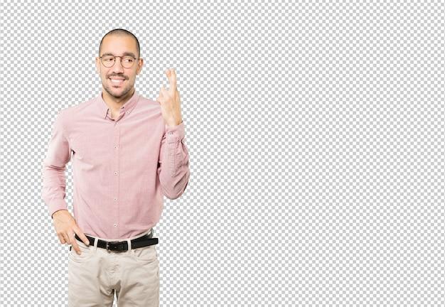 Hombre joven preocupado haciendo un gesto de dedos cruzados